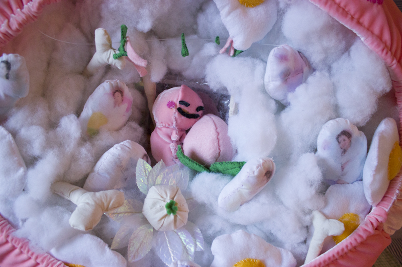 Close up of inside of Kirby's mouth, showing fabric bones, felt eggs, images of pregnant women with maternity pillows printed onto miniature pillows, and a handmade embryonic kirby that has a tadpole-like body.